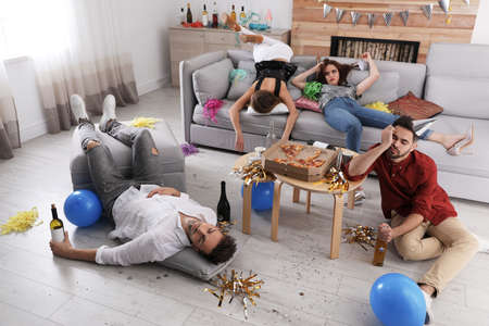 Drunk friends sleeping in messy room after party Stok Fotoğraf - 137882726