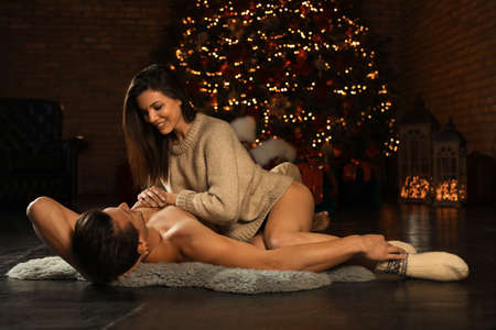 Passionate young couple enjoying each other near Christmas tree at home