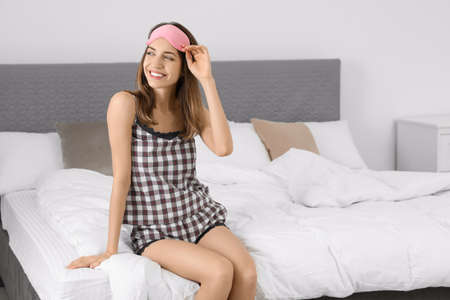 Beautiful woman wearing pajamas and sleep mask indoors. Bedtime Stok Fotoğraf - 137882781