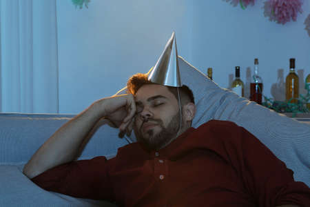Young man with cap sleeping on sofa in room after party
