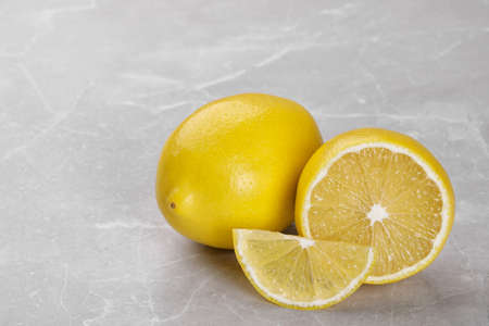Whole and cut fresh ripe lemons on grey marble table