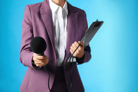 Professional journalist with clipboard and microphone on light blue background, closeup. Space for text
