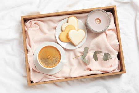 Aromatyczna kawa i ciasteczka na łóżku, leżące na płasko. Romantyczne śniadanie