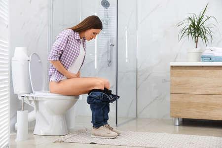Vrouw lijdt aan aambei op toiletpot in toilet