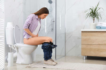 Woman suffering from hemorrhoid on toilet bowl in rest room