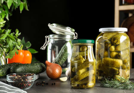 Glass jars of pickled cucumbers on grey table