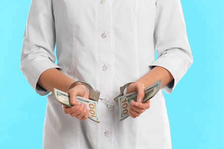 Doctor in handcuffs with bribe on light blue background, closeup. Corrupted medicine