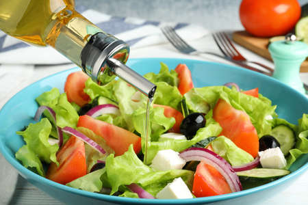 Adding cooking oil to delicious salad on table, closeup