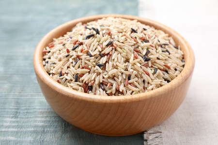 Mix of different brown rice in bowl on light blue wooden table