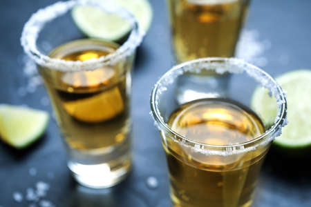 Mexican Tequila shots with salt and lime slices on grey table, closeup