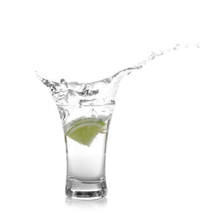 Splashing Mexican Tequila in shot glass with lime slice isolated on white Stockfoto