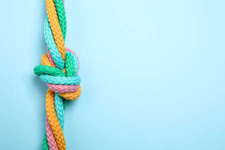 Top view of colorful ropes tied together on light blue background, space for text. Unity concept Archivio Fotografico