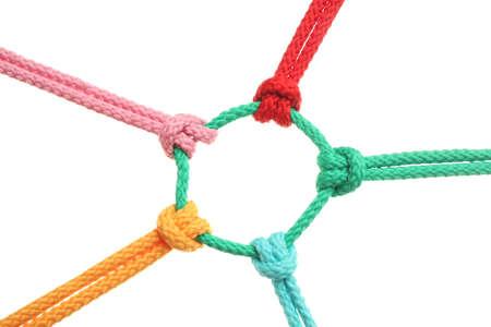 Cuerdas de colores atados juntos sobre fondo blanco. Concepto de unidad