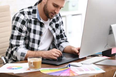 Male designer working at desk in office