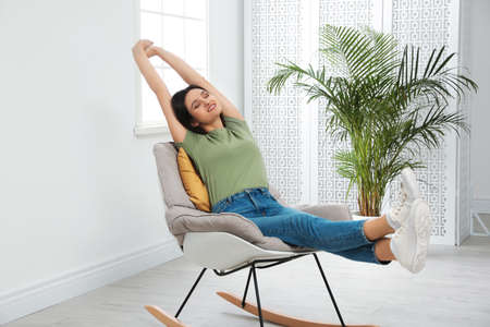 Young woman relaxing in rocking chair at home Stok Fotoğraf