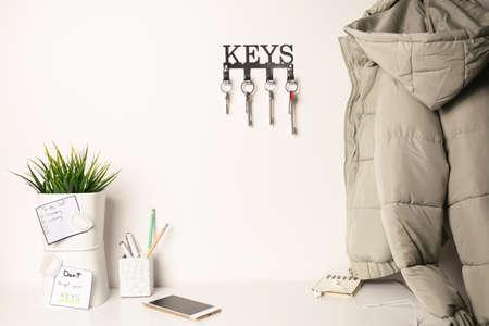 Schlüsselhalter aus Metall an heller Wand im Innenbereich Standard-Bild