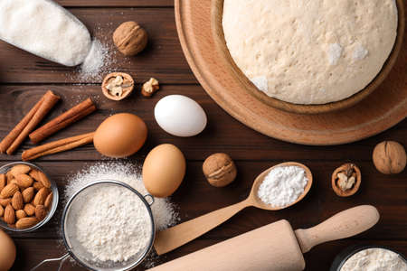 Dough and ingredients for pastries on wooden table, flat lay Stock Photo
