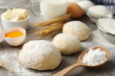 Dough and other ingredients for pastries on light grey table