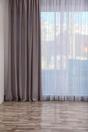 Window with elegant curtains in empty room Stockfoto