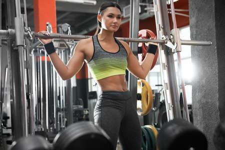 Junge Frau, die an der Smith-Maschine im modernen Fitnessstudio trainiert