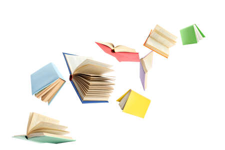Colorful hardcover books flying on white background