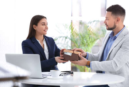 Man giving bribe to woman at table in office Stock Photo