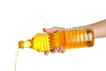Woman pouring cooking oil from bottle on white background, closeup