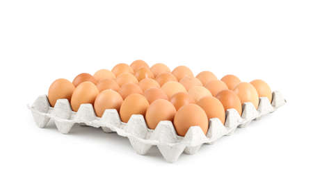 Raw chicken eggs in carton tray isolated on white