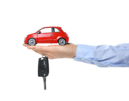 Man holding key and miniature automobile model on white background, closeup. Car buying