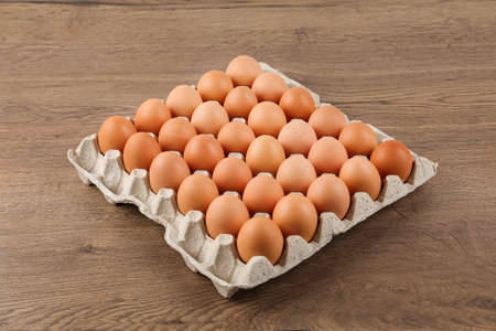 Raw chicken eggs in carton tray on wooden table