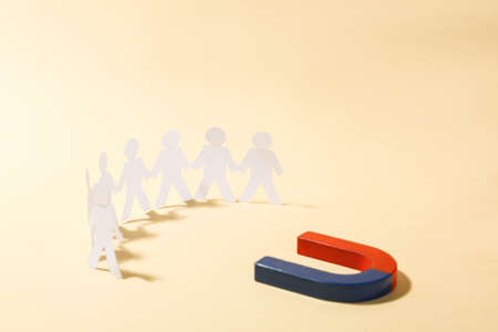 Magnet attracting paper people on beige background