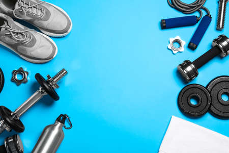 Gym equipment on light blue background, flat lay. Space for text
