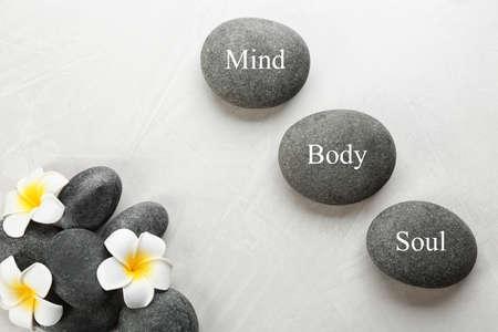 Steine mit Worten MIND, BODY, SOUL und Blumen auf hellem Hintergrund, flach. Zen-Lebensstil Standard-Bild