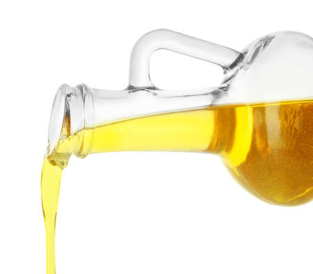 Pouring cooking oil from pitcher isolated on white