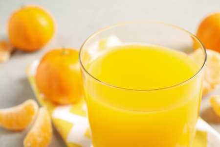 Glass of fresh tangerine juice, closeup view