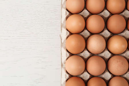 Raw chicken eggs on white wooden table, top view