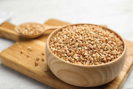 Uncooked green buckwheat grains on wooden board