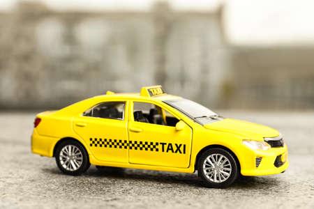 Yellow taxi car model on city street