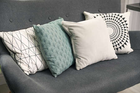 Stylish decorative pillows on grey couch, closeup