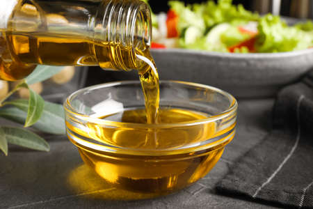 Pouring cooking oil into bowl on grey table, closeup