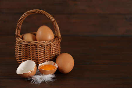 Raw chicken eggs and feather on wooden table. Space for text