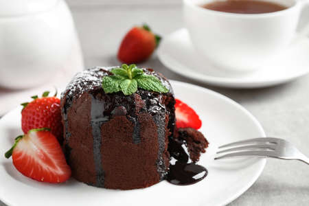 Delicious warm chocolate lava cake with mint and strawberries on table, closeup Фото со стока