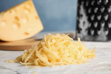 Tasty grated cheese on white wooden table, closeup Stock fotó