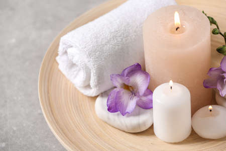 Beautiful composition with spa stones and burning candles on grey table, closeup Stock Photo