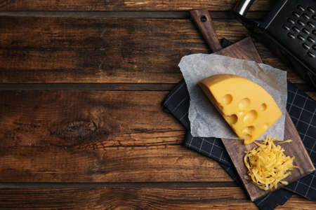 Tasty grated cheese on wooden table, flat lay. Space for text