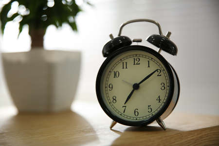 Alarm clock on wooden table at home. Morning time Imagens