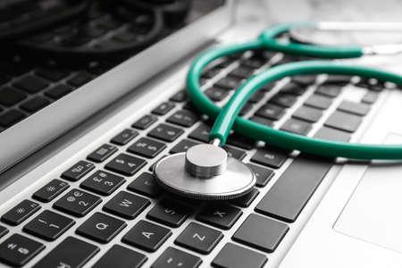 Stethoskop auf Laptop, Nahaufnahme. Konzept des technischen Supports