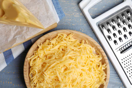 Tasty grated cheese on light grey wooden table, flat lay