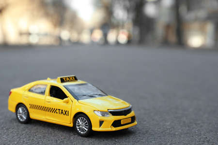 Yellow taxi car model on city street. Space for text