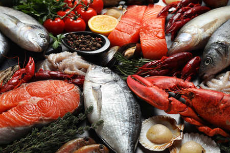 Fresh fish and different seafood on table, closeup